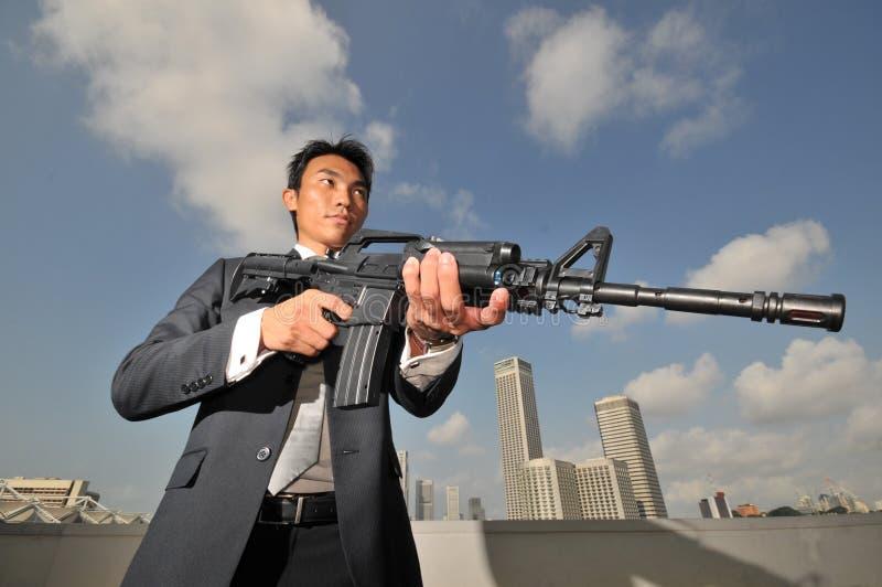 Asiatischer chinesischer Mann, der ein starkes Gewehr trägt lizenzfreies stockbild