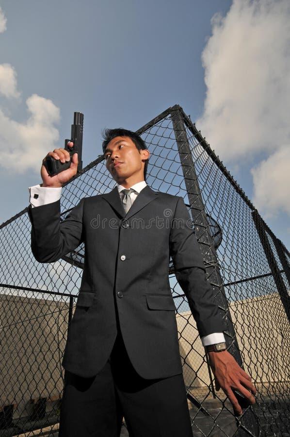 Asiatischer chinesischer Mann, der eine Pistole trägt stockfoto