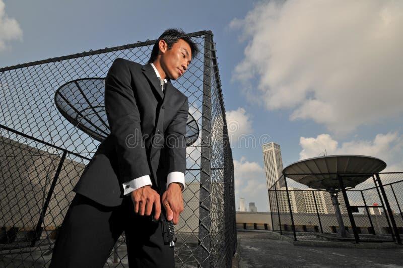 Asiatischer chinesischer Mann, der eine Pistole trägt lizenzfreie stockfotos