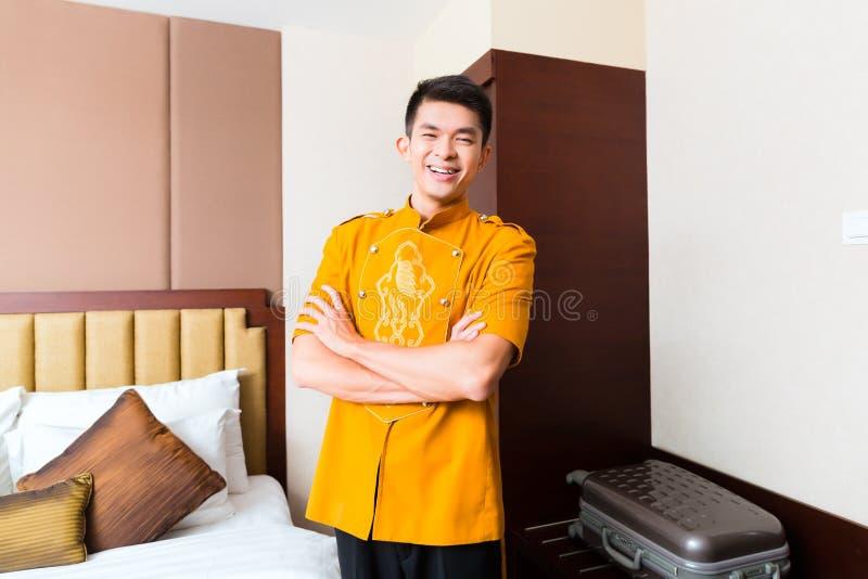 Asiatischer chinesischer Träger, der Koffer zum Luxushotelraum holt lizenzfreie stockfotografie
