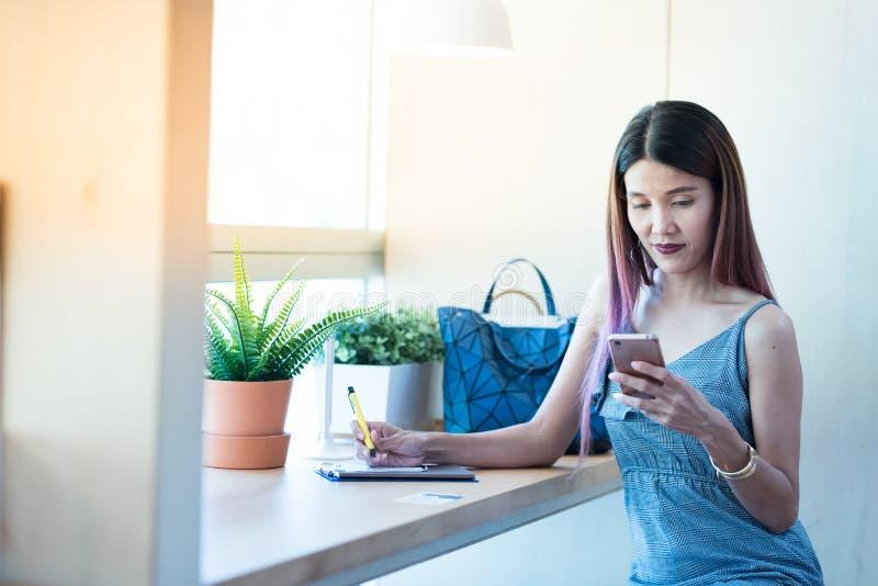 Asiatischer Damengebrauch und -gespräch im intelligenten Handy beim Sitzen in c stockbilder