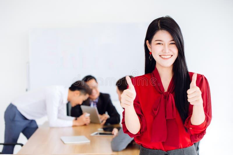 Asiatischer Daumen Geschäftsmädchen-CEO-Show zwei Handherauf gutes zusammenarbeiten stockfoto