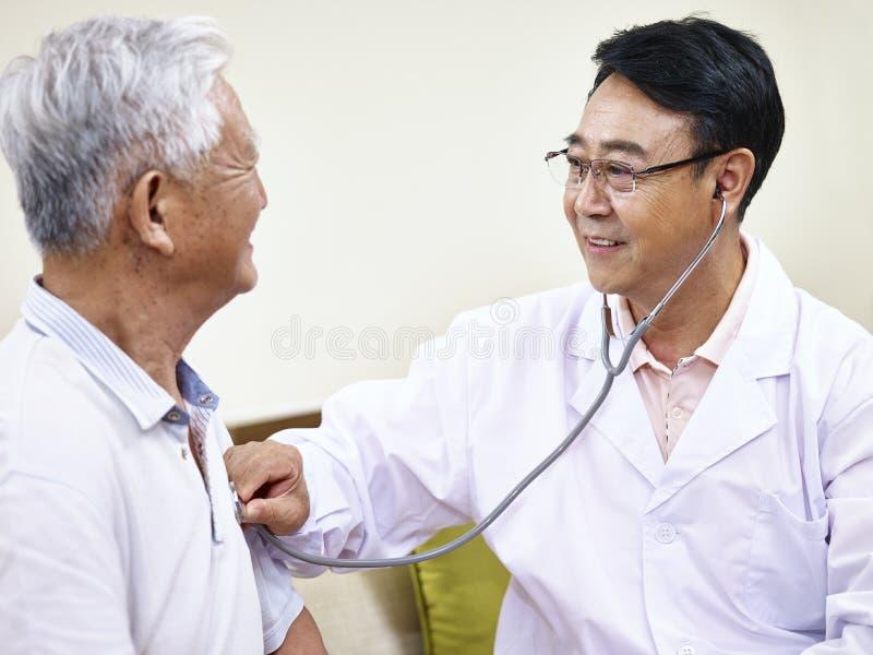 Asiatischer Doktor, der älteren Patienten überprüft lizenzfreies stockfoto