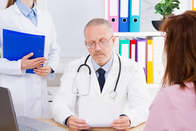 Asiatischer Doktor schreibt Behandlung für seinen weiblichen Patienten in einem Ärztlichen Dienst vor lizenzfreie stockfotos