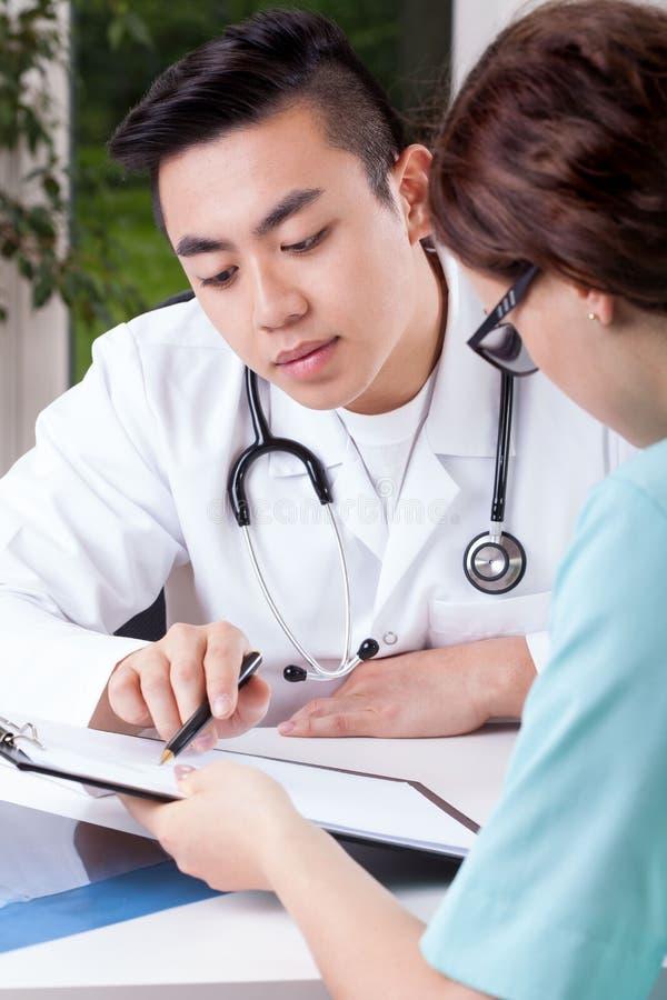 Asiatischer Doktor und sein Assistent stockbild