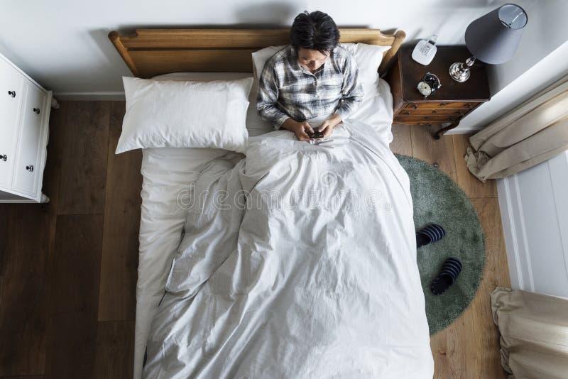 Asiatischer Ethniekerl, der Telefon auf dem Bett verwendet stockbilder