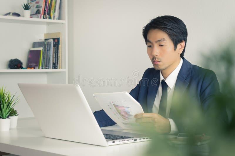 Asiatischer Finanzberater oder Asiatischer Berater Businessman Analyze Financial Report in Vintage Tone stockbild