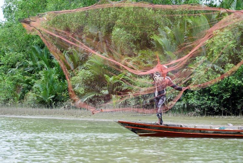 Asiatischer Fischer auf hölzernem Boot stockbild