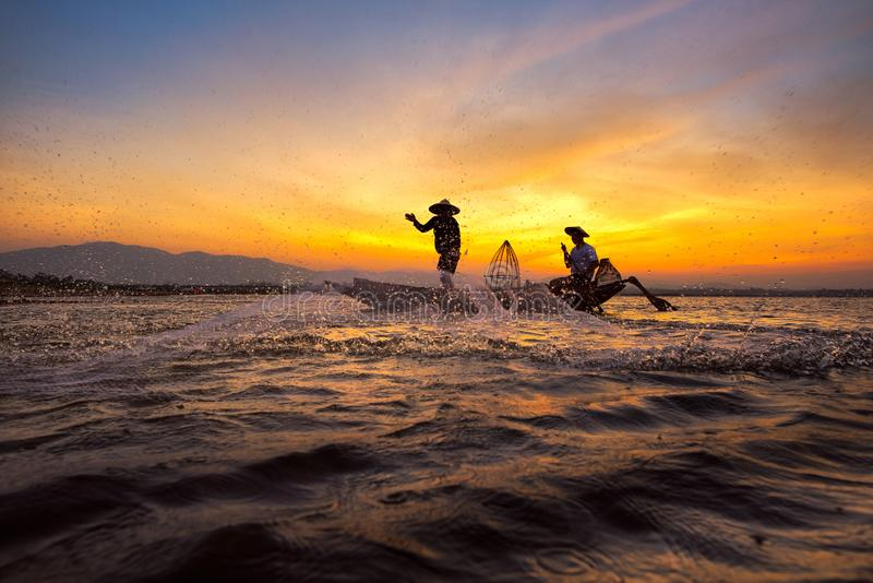 Asiatischer Fischer des Schattenbildes auf hölzernem Boot lizenzfreie stockfotografie