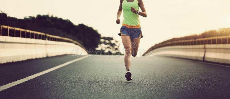 Asiatischer Frauenläufer der Eignung, der auf Stadtstraße läuft stockbilder