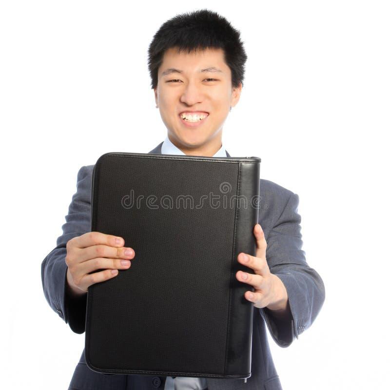 Asiatischer Geschäftsmann, der eine lederne Mappe anhält lizenzfreies stockfoto