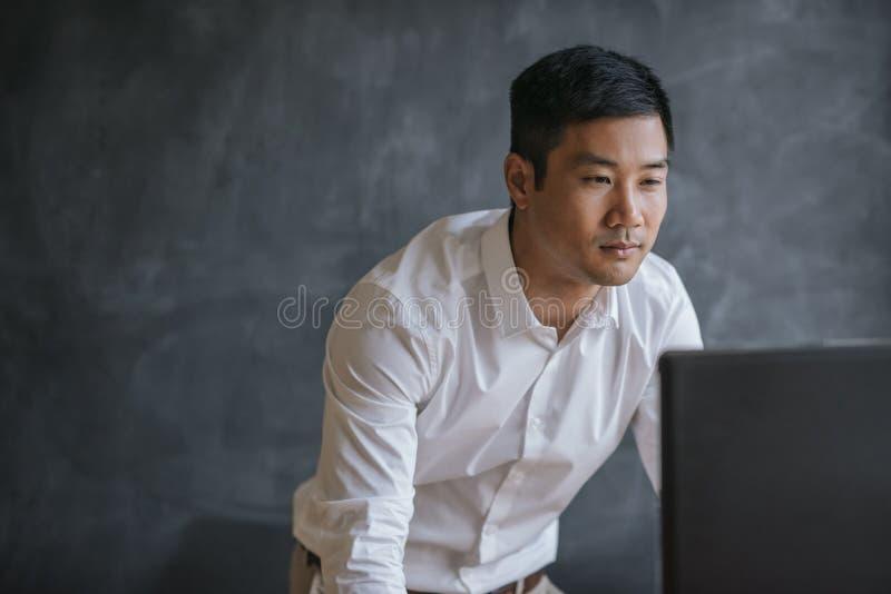 Asiatischer Geschäftsmann, der an einem Computer in einem Büro arbeitet lizenzfreies stockfoto