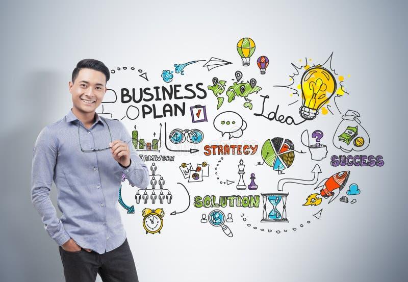 Asiatischer Geschäftsmann, der Gläser, Unternehmensplan hält lizenzfreies stockfoto
