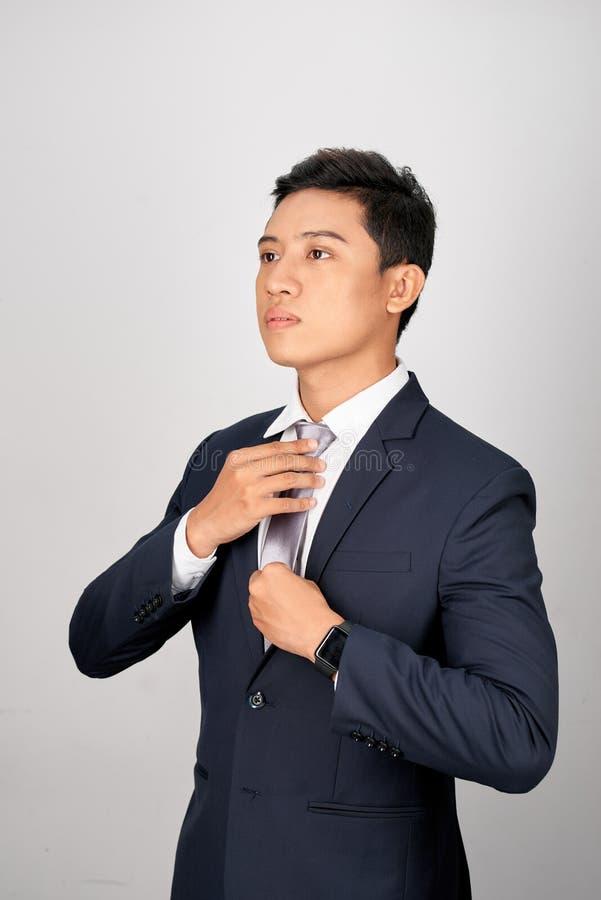 Asiatischer Geschäftsmann, der graue Bindung, auf weißem Hintergrund justiert stockfoto