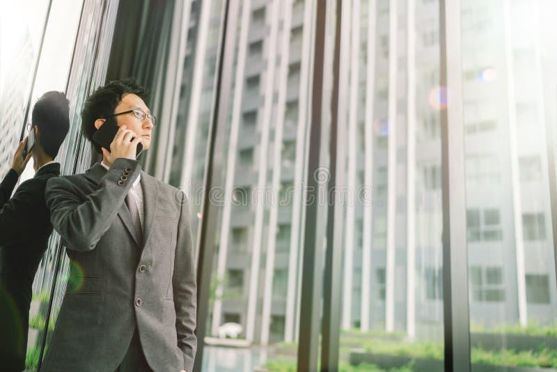 Asiatischer Geschäftsmann, der Handy, Geschäft oder Kommunikationstechnologiekonzept, mit Blendenfleckeffekt- und Kopienraum verw lizenzfreie stockfotografie