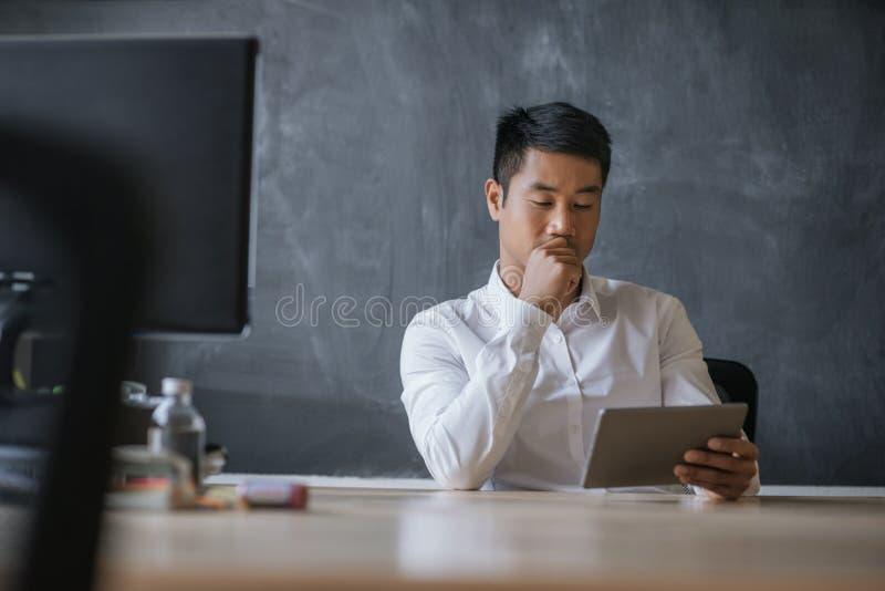 Asiatischer Geschäftsmann, der an seiner Schreibtischfunktion auf einer Tablette sitzt lizenzfreies stockfoto