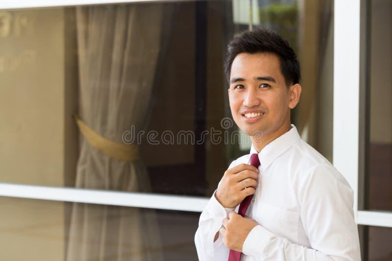 Asiatischer Geschäftsmann, der seins Bindung geraderichtet stockbilder