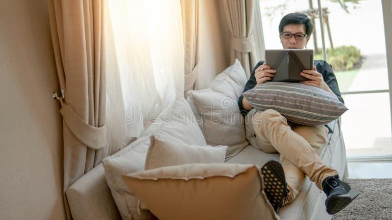 Asiatischer Geschäftsmann, der Tablette im Wohnzimmer verwendet lizenzfreies stockfoto