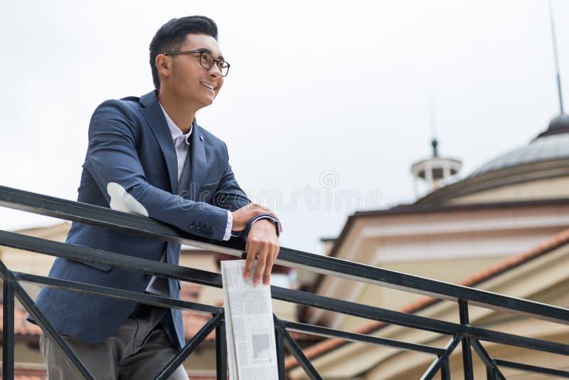Asiatischer Geschäftsmann, der Zeitung hält stockfotografie