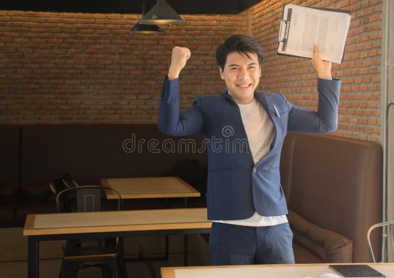 Asiatischer Geschäftsmann froh, das Triumphieren mit den angehobenen Händen zu gewinnen und zu folgen lizenzfreies stockbild