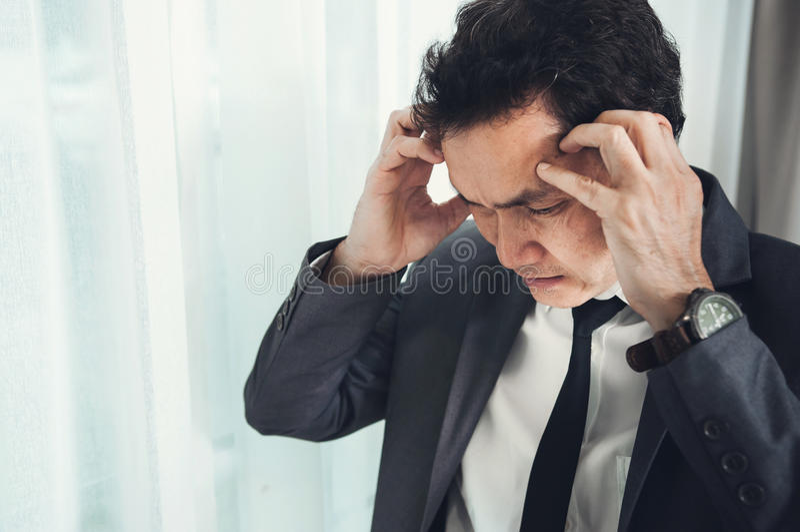 Asiatischer Geschäftsmann hat Kopfschmerzen von der Migräne von überarbeitetem IL lizenzfreie stockfotos