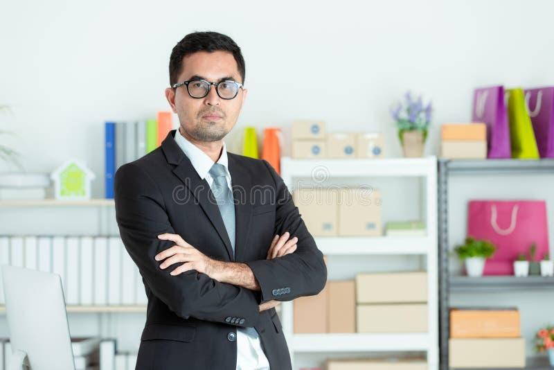 Asiatischer Geschäftsmann im Klagenlächeln, das zu den Smartphones und zum sitti schaut lizenzfreie stockfotografie