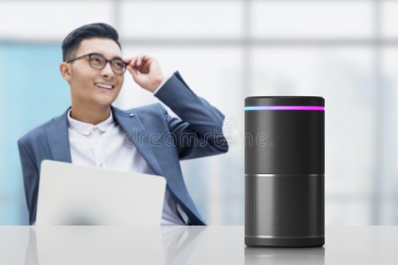 Asiatischer Geschäftsmann mit intelligentem Sprecher lizenzfreie stockfotografie