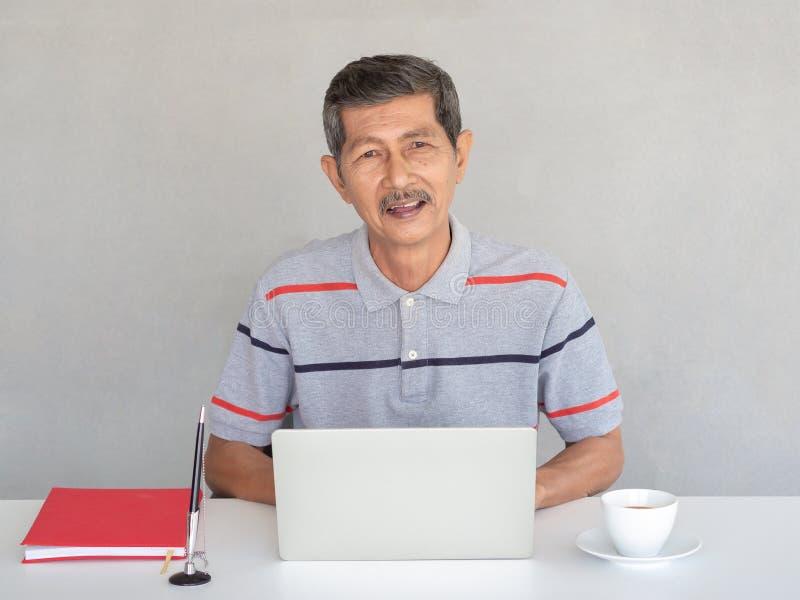 Asiatischer Geschäftsmann, Senioren genießen, Laptops auf einer weißen Tabelle zu verwenden Mit einem Stift und einem roten Bu stockfotografie
