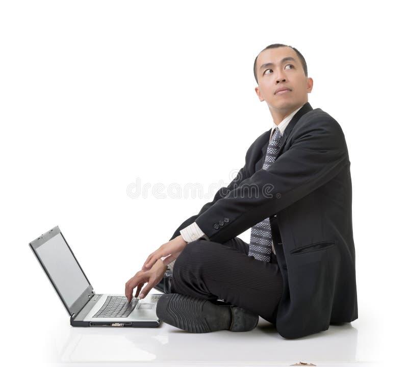 Asiatischer Geschäftsmann unter Verwendung des Laptops auf dem Boden, der zurück schaut lizenzfreie stockfotos
