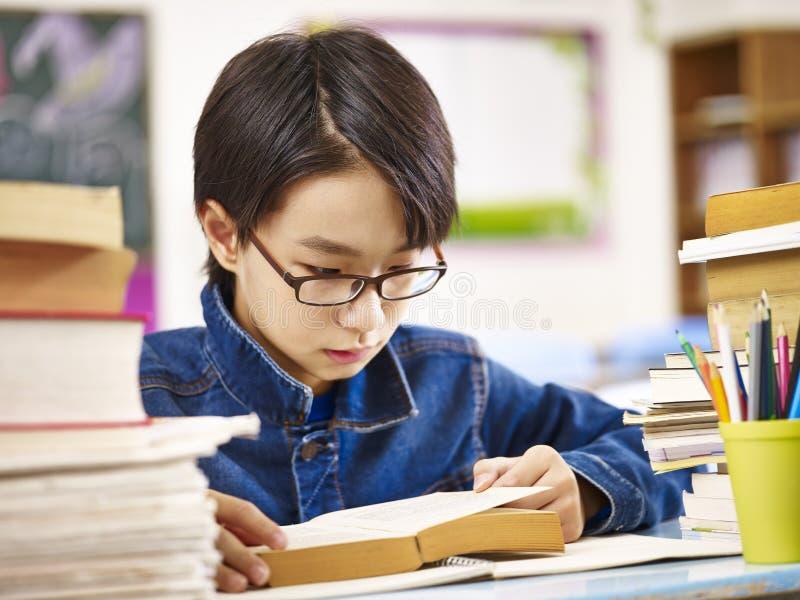 Asiatischer grundlegender Schüler, der ein Buch liest stockbild