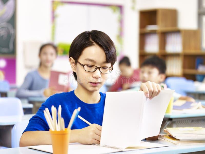 Asiatischer Grundschulestudent, der in der Klasse studiert stockbilder
