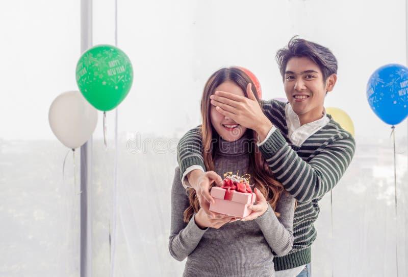 Asiatischer gut aussehender Mann schließt seine Augen und Schläge von hinten, um sie über das Weihnachtsgeschenk zu überraschen L stockbilder