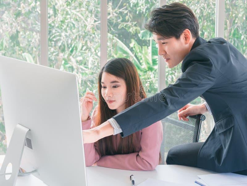 Asiatischer hübscher junger Geschäftsmannpunkt, zum des Monitors auszusortieren stockbild