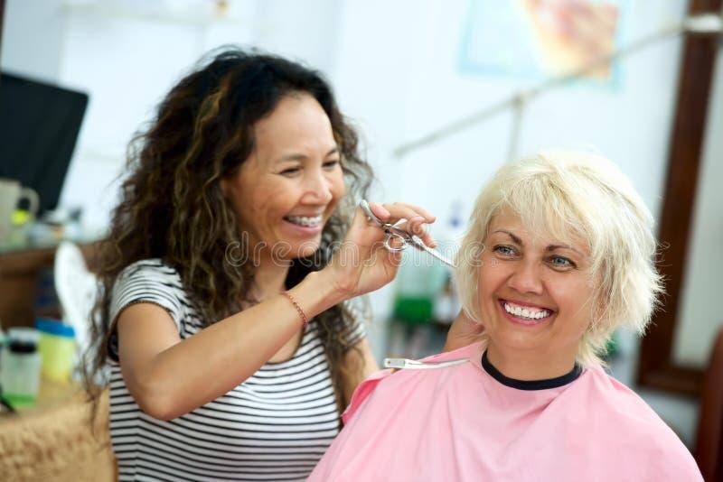 Asiatischer Hauptfriseur schneidet Haar stockfotos