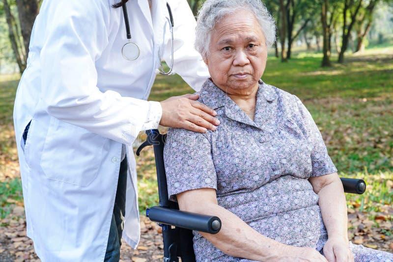 Asiatischer heller Gesichtspatient des älteren oder älteren Frauenlächelns alter Dame auf Rollstuhl im Park stockfoto