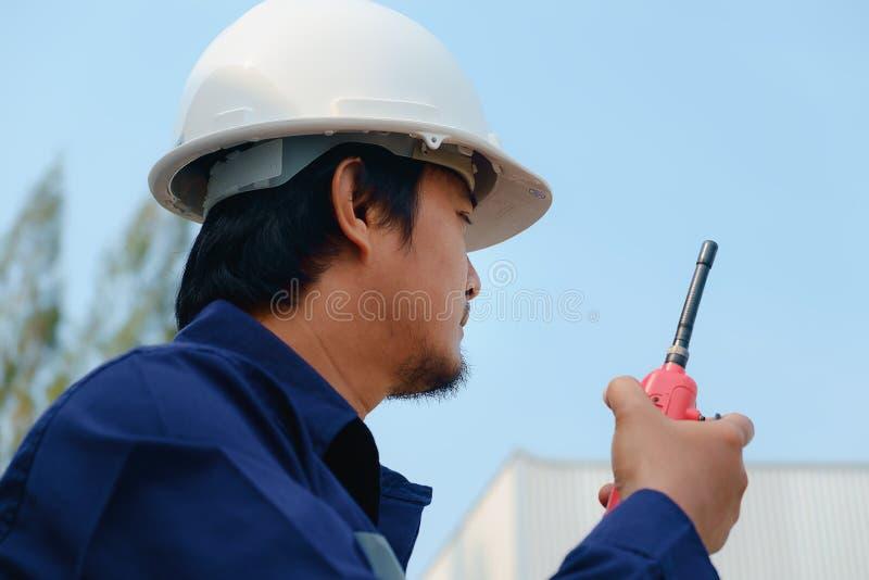 Asiatischer Ingenieur in der blauen Sicherheitskragenuniform und in der weißen Sicherheit lizenzfreie stockfotografie