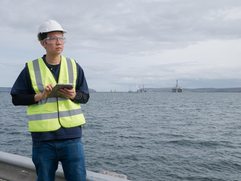 Asiatischer Ingenieur, der eine Tablette und eine Stellung hält stockbild
