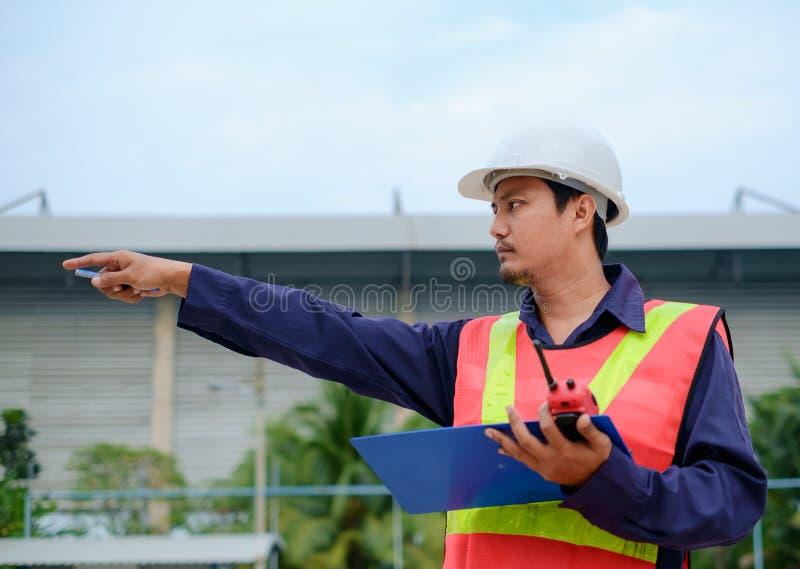 Asiatischer Ingenieur in der Sicherheitsuniform und im weißen Sturzhelm seinen Finger auf unscharfem Industriebetriebshintergrund stockfoto