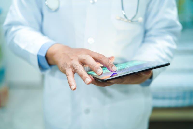 Asiatischer intelligenter Manndoktor, der digitale Tablettentechnologie hält, um Wissen zu suchen, Behandlung zu lösen lizenzfreies stockfoto