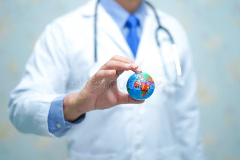 Asiatischer intelligenter Manndoktor, der eine Kugel hält: gesundes starkes medizinisches Konzept stockfotografie