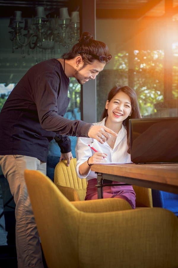 Asiatischer jüngerer freiberuflich tätiger Mann und Frau, die mit lächelndem Gesicht arbeitet lizenzfreie stockfotografie