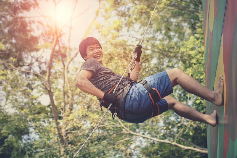 Asiatischer jüngerer Mann, der am Klipp wandert Sicherheit Seil und laughin hängt stockfotos