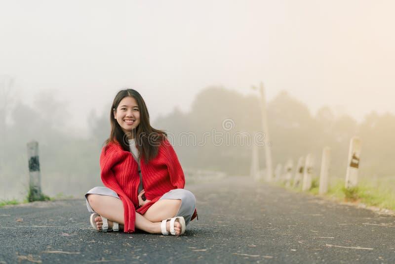 Asiatischer Jugendlicher, der eine rote Strickjacke morgens sitzt mitten in der Stra?e durch den Nebel des Reservoirs tr?gt lizenzfreies stockfoto