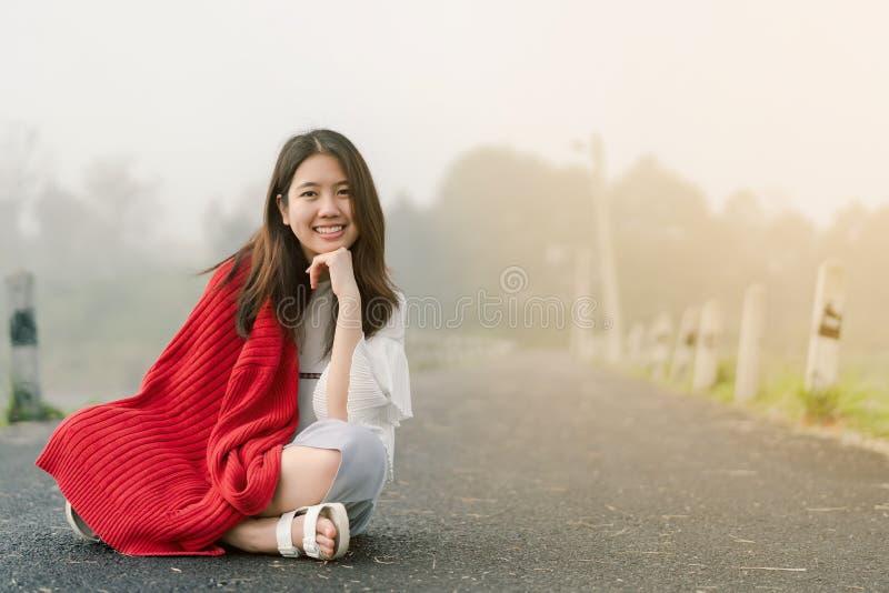Asiatischer Jugendlicher, der eine rote Strickjacke morgens sitzt mitten in der Stra?e durch den Nebel des Reservoirs tr?gt lizenzfreie stockbilder