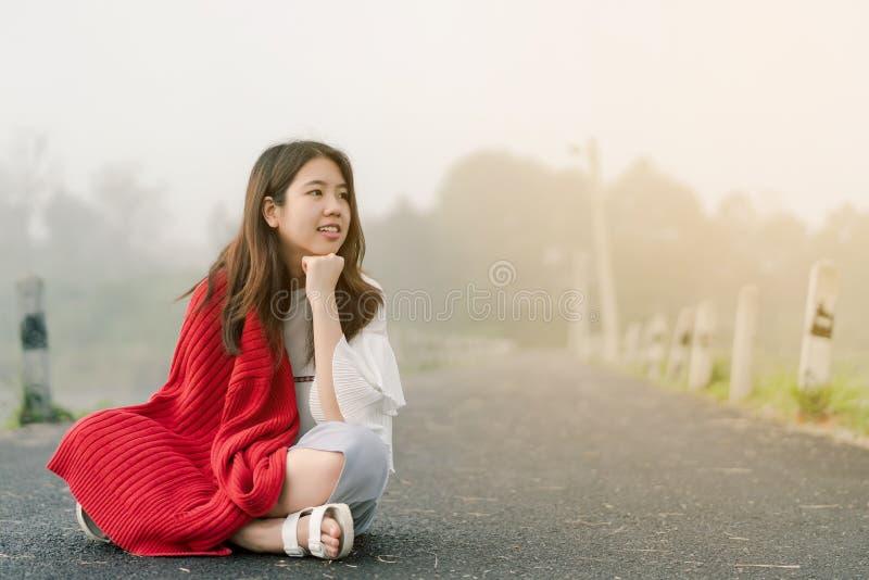 Asiatischer Jugendlicher, der eine rote Strickjacke morgens sitzt mitten in der Stra?e durch den Nebel des Reservoirs tr?gt lizenzfreie stockfotografie