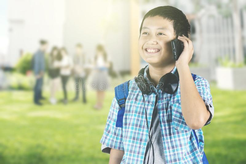 Asiatischer jugendlicher Schüler, der am Telefon spricht stockbild