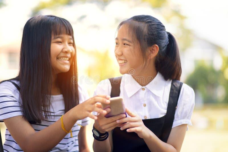 Asiatischer Jugendlicher zwei, der mit Gl?ckgesichts-Lesemitteilung auf intelligentem Telefonschirm lacht lizenzfreie stockfotografie