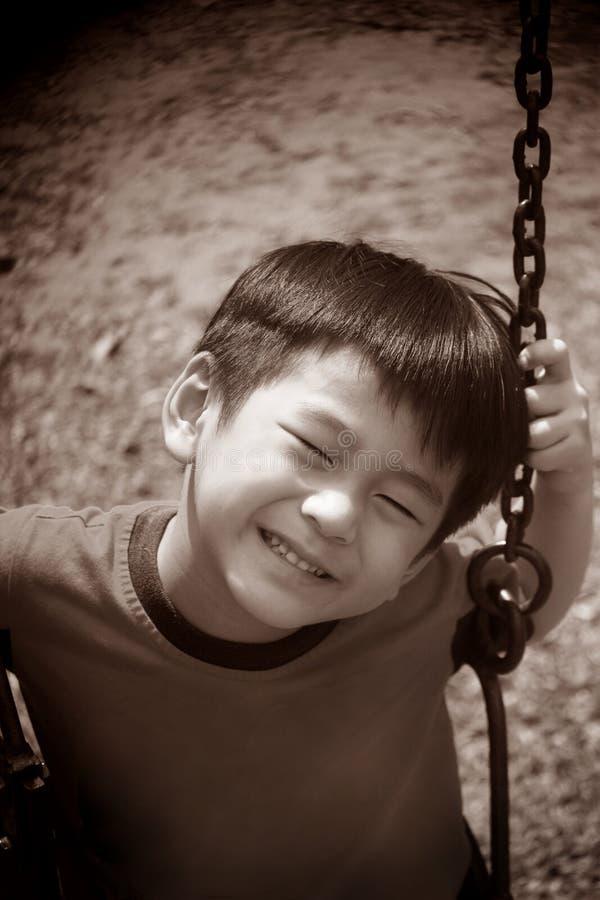 Asiatischer Junge Auf Einem Schwingen Stockbilder