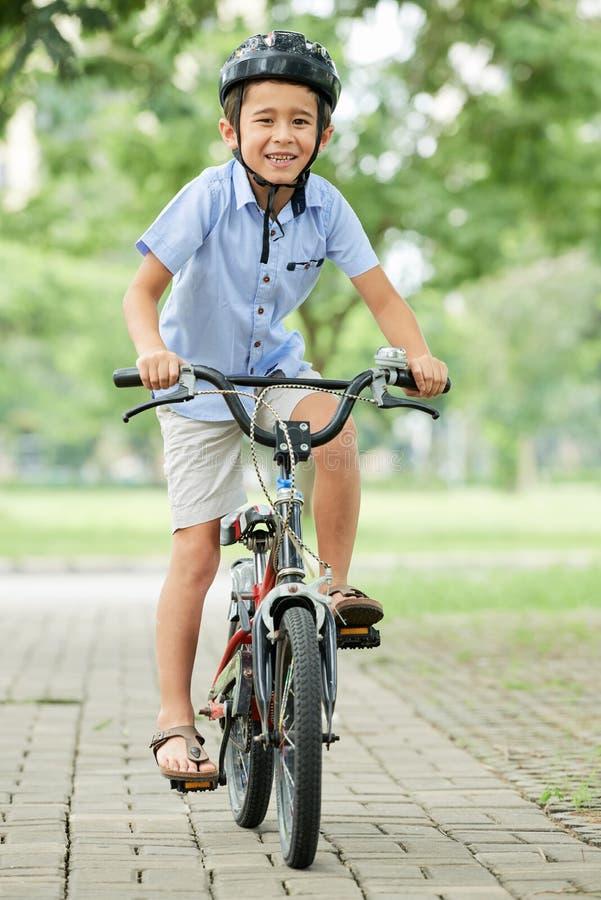 Asiatischer Junge auf Fahrrad im Park stockfotografie