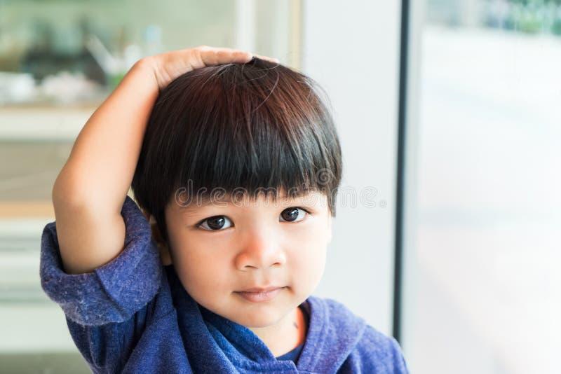 Asiatischer Junge berührt sein Kopf- und Haardenken stockbilder